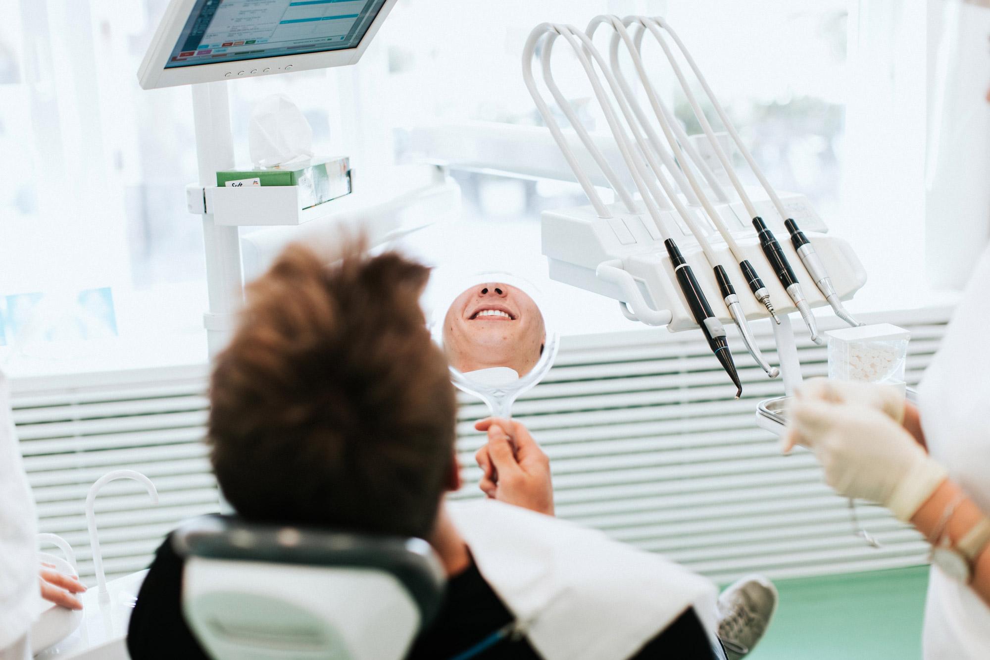osmijeh pacijenta koji izbjeljuje zube u ogledalu